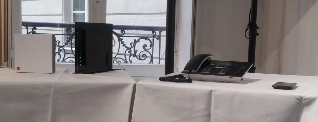 De gauche à droite : le routeur de services, le modem câble pour la connexion à 200 Mbit/s, un poste téléphonique directement connecté au réseau mobile de SFR et un smartphone. Le quaduple play professionnel selon Numericable-SFR.